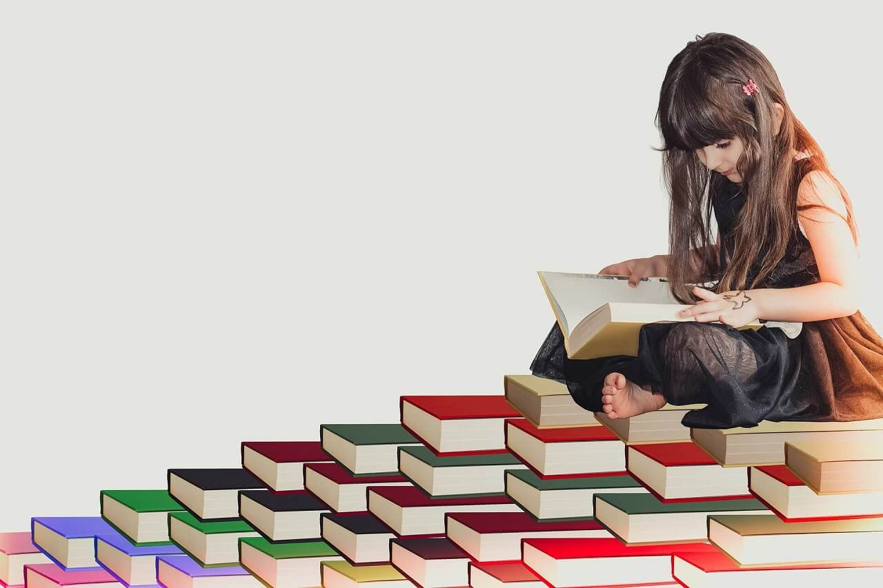 Girl reading on a stack of books